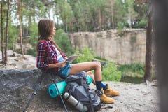 jonge wandelaarvrouw met rugzak en trekkingspolen die tablet gebruiken stock foto