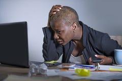 Jonge wanhopige en beklemtoonde Afrikaanse Amerikaanse bedrijfsvrouw die bij laptop computerbureau op kantoor werken die aan span stock fotografie