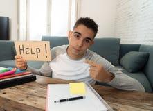 Jonge wanhopige student in en spanning die houdend een hulpteken werken bestuderen royalty-vrije stock foto's
