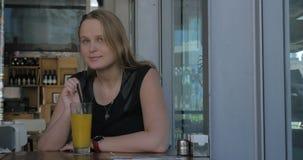 Jonge weemoedige vrouw die drank in koffie hebben stock videobeelden