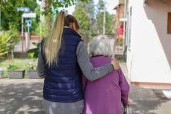 Jonge werker uit de hulpverlening die met het bejaarde in de tuin lopen royalty-vrije stock foto