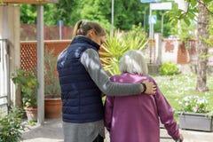 Jonge werker uit de hulpverlening die met het bejaarde in de tuin lopen stock foto's
