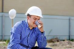 Jonge werkmans nippende koffie op een bouwterrein Stock Foto's