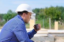 Jonge werkmans nippende koffie op een bouwterrein Royalty-vrije Stock Foto