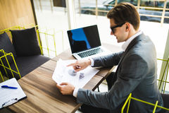 Jonge werknemer die computermonitor met documenten tijdens werkdag in bureau bekijken stock afbeeldingen