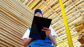 Jonge werknemer die een inventaris van voorraad op hout maken stock videobeelden