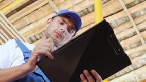 Jonge werknemer die een inventaris van voorraad op hout maken stock footage