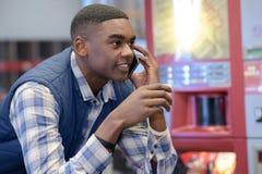 Jonge werknemer die telefoon in pakhuis met behulp van stock afbeeldingen