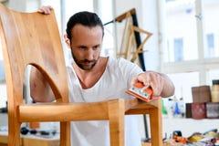 Jonge werknemer in een timmerliedenworkshop met houten stoel stock foto