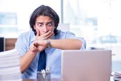Jonge werknemer ongelukkig met het bovenmatige werk royalty-vrije stock afbeelding