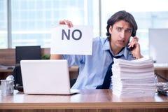 Jonge werknemer ongelukkig met het bovenmatige werk stock foto