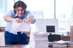 Jonge werknemer ongelukkig met het bovenmatige werk stock afbeelding