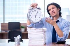Jonge werknemer ongelukkig met het bovenmatige werk stock afbeeldingen