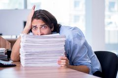 Jonge werknemer ongelukkig met het bovenmatige werk royalty-vrije stock foto