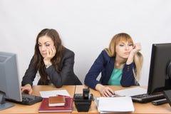 Jonge werknemer twee van het bureau achter een bureau die droevig in het kader kijken stock foto