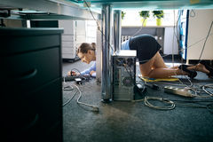 Jonge werknemer verbindende kabels en draden aan computer in bureau Royalty-vrije Stock Foto's
