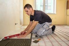 Jonge werknemertegelzetter die keramische tegels installeren die hefboom gebruiken op cementvloer met het verwarmen van het rode  stock afbeelding
