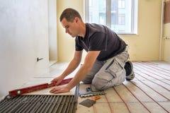 Jonge werknemertegelzetter die keramische tegels installeren die hefboom gebruiken op cementvloer met het verwarmen van het rode  royalty-vrije stock foto's