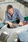 Jonge werktuigkundige die oude motor van een auto herstellen royalty-vrije stock afbeelding