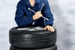 Jonge werktuigkundige in eenvormig met moersleutel en wielen Royalty-vrije Stock Foto's