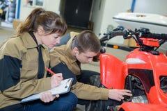 Jonge werktuigkundigen die quadbike onderzoeken stock foto