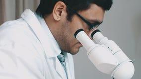 Jonge wetenschapper die door de microscoop kijken stock footage