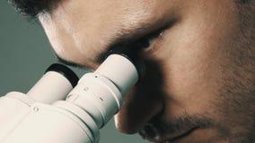 Jonge wetenschapper die door de microscoop kijken stock video