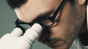 Jonge wetenschapper die door de microscoop kijken stock videobeelden
