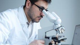 Jonge wetenschapper die door microscoop kijken stock footage