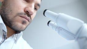 Jonge wetenschapper die door microscoop kijken stock video