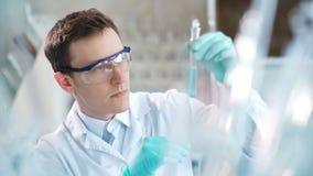 Jonge wetenschapper die reageerbuizen in het laboratorium controleren De mens draagt veiligheidsbrillen stock videobeelden