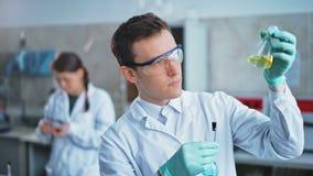 Jonge wetenschapper die reageerbuizen in het laboratorium controleren De mens draagt veiligheidsbrillen stock video