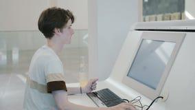 Jonge wetenschapper in modern wetenschappelijk centrum Online Wetenschappelijke Bibliotheek van de Universiteit stock footage