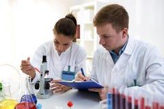 Jonge wetenschappers die test of onderzoek naar schoollaboratorium maken stock foto's