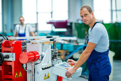 Jonge witte arbeider in fabriek die machine met behulp van royalty-vrije stock foto's