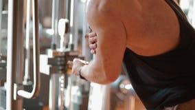 Jonge witte bodybuilder opleidingsbicepsen in de gymnastiek stock videobeelden