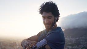 Jonge witte donkerbruine mens in zijn trainingkleren die de muziek veranderen die van zijn telefoon op zijn armband bij zonsopgan stock video