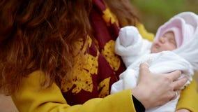 Jonge witte vrouw met een pasgeboren baby op haar handen stock video