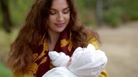 Jonge witte vrouw met een pasgeboren baby op haar handen stock footage