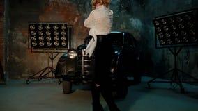 Jonge witte vrouwelijke danser in studio dichtbij de retro auto stock footage