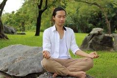 Jonge yogimens die yogameditatie doen terwijl het zitten in lotusbloempositie inzake de rots in het park royalty-vrije stock foto