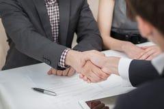 Jonge zakenlieden die handen met elkaar in de zaken schudden Stock Foto