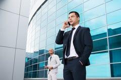Jonge zakenlieden in donkere die kostuums en helder, lachend en zich verheugt aan het nieuws door de mobiele telefoon wordt ontva Royalty-vrije Stock Fotografie
