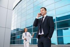 Jonge zakenlieden in donkere die kostuums en helder, lachend en zich verheugt aan het nieuws door de mobiele telefoon wordt ontva Royalty-vrije Stock Foto's