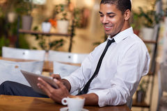 Jonge zakenman in de koffiepauze die aan zijn ipad werken stock afbeelding