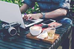 Jonge zakenman die aan laptop bij tuin werken stock afbeelding
