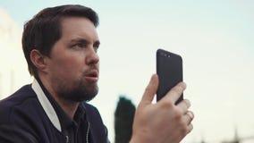 Jonge zakenman die aan partner op telefoon in openlucht in de dag spreken stock footage