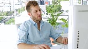 Jonge zakenman die aan zijn computer werken stock video