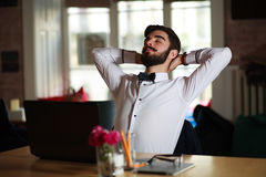 Jonge zakenman die bij de werkplaats, in bureau rusten Stock Afbeeldingen