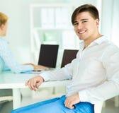 Jonge zakenman die in bureau werken, die zich dichtbij bureau bevinden Royalty-vrije Stock Afbeelding